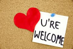 You Are wellcome sign written on sticky note pinned on pinboard with rd heart Stock Images