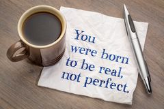You were born to be real, not perfect. Inspirational reminder - handwriting on a napkin with a cup of coffee Royalty Free Stock Photos