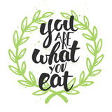 You are what you eat, modern ink brush calligraphy with wreath. Royalty Free Stock Photo