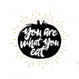 You are what you eat - quote inside the tomato. Vegetable themed sign, badge, label. Typography design Royalty Free Stock Photography