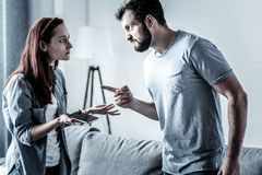 Angry unshaken man standing and pointing at his wife. You will be sorry. Angry unshaken furious men standing in the bright room feeling stressful himself and Stock Photography