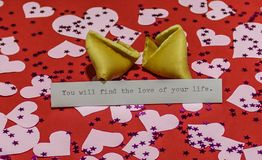 `You will find the love of your life` message in broken fortune cookie on red background covered with harts. And sparkles Royalty Free Stock Image