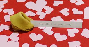 `You will find true love` message in fortune cookie on red background covered with harts. `You will find true love` message in fortune cookie on red background Royalty Free Stock Photography