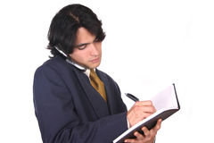 You will have it on time. A man writing in his notebook and talking by celphone Royalty Free Stock Image