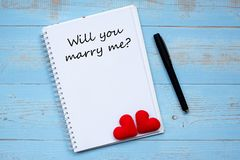 YOU WILL MARRY ME? word on notebook and pen with couple red heart shape decoration on blue wooden table background. Wedding, stock photos