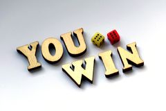 You win. Wooden letters and dice on a white background. Stock Image