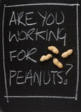 Are You Working for Peanuts?. The phrase Are You Working for Peanuts on a blackboard with peanuts in their shells as a concept for being underpaid and looking Stock Photos