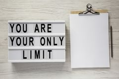 `You are your only limit` words on a lightbox, clipboard with blank sheet of paper over white wooden background, top view.  stock photography