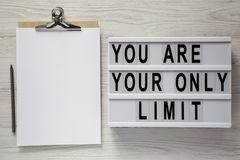 `You are your only limit` words on a lightbox, clipboard with blank sheet of paper over white wooden surface, top view.  royalty free stock images