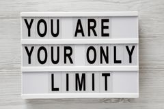 `You are your only limit` words on a lightbox over white wooden background, top view. Overhead, from above. Flat lay.  stock images