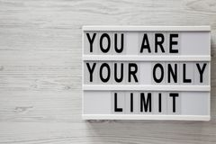 `You are your only limit` words on a modern board over white wooden background, top view. Overhead, from above. Flat lay. Copy. Space royalty free stock photography