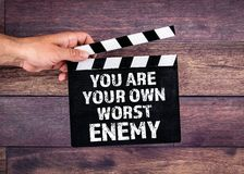 You Are Your Own Worst Enemy. Hand holding movie clapper stock photo