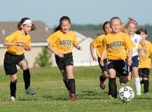 youg足球运动员控制球作为她为目标赛跑 库存照片
