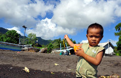 Youg boy playing kite. With a metal box in amed village bali Stock Photos