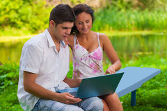 Youg couple loking in laptop on nature Stock Photo
