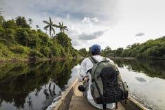 Youg-Mann, der an Bord eines Kanus im Amazonas-Dschungel sitzt lizenzfreie stockfotos