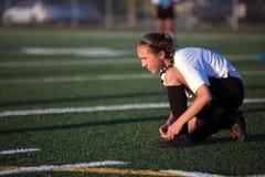 Youg piłki nożnej dziewczyny sznurowania buty na polu Fotografia Stock