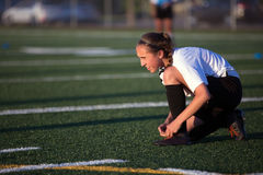 Youg soccer girl lacing shoes on the field. Soccer field Stock Photography