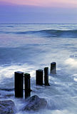Youghal Bay. Waves at sunset breaking over foreground rocks and breakwaters at Youghal, Co.Cork, Ireland Royalty Free Stock Images