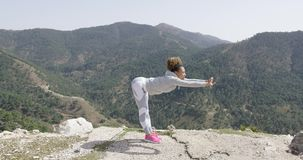 Yougn female stretching on rock stock video footage