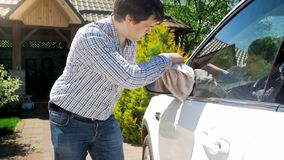 Yougn male driver cleaning car mirror with rag. Male driver cleaning car mirror with rag Stock Image