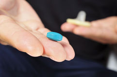 Yougn man with blue pill and condom. Closeup of a young man with a blue pill in one hand and a condom in the other hand Royalty Free Stock Photos