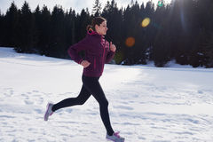 Yougn woman jogging outdoor on snow in forest Royalty Free Stock Image