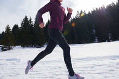Yougn woman jogging outdoor on snow in forest Stock Photos