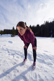 Yougn woman jogging outdoor on snow in forest Royalty Free Stock Photo