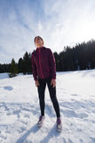 Yougn woman jogging outdoor on snow in forest Royalty Free Stock Photos