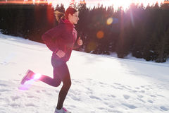 Yougn woman jogging outdoor on snow in forest Stock Image