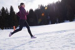 Yougn woman jogging outdoor on snow in forest Royalty Free Stock Images
