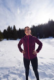 Yougn woman jogging outdoor on snow in forest Stock Photo