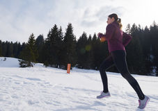 Yougn woman jogging outdoor on snow in forest Stock Images