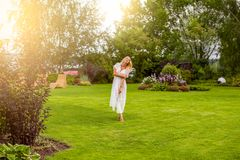 Youmg beautiful blond woman in beautiful summer garden is barefoot on lawn stock photos