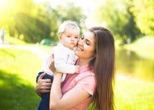 Youmg behandla som ett barn den lyckliga kvinnan som spelar med hennes gulligt, i solig sommar parkerar utomhus- Mothercare bild Fotografering för Bildbyråer