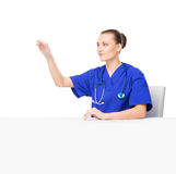 A youmg female medical worker pointing at something Royalty Free Stock Image