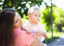Youmg happy woman playing with her cute baby in summer sunny park outdoor. Mothercare picture Stock Image