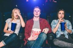 Youn男人和妇女在椅子和观看的电影坐 他们惊奇并且被混淆 白肤金发的女孩投入了她的手 免版税库存图片