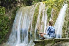 Привлекательная женщина youn во время раздумья около водопада Стоковая Фотография
