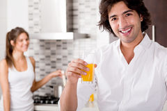 Youn couple cheersing. Young man smile in the kitchen royalty free stock photography