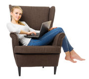 Youn flicka med bärbara datorn i stol royaltyfria bilder