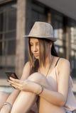 Youn flicka med den smarta telefonen Fotografering för Bildbyråer