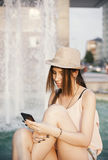 Youn flicka med den smarta telefonen Arkivfoton