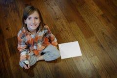 Youn Girl på det Wood golvet med papper och pennan Royaltyfri Foto