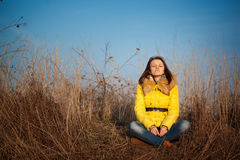 Youn girl sitting on yellow autumn grass Stock Photo