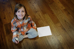 Youn Girl on Wood Floor with Paper and Pen Royalty Free Stock Photo