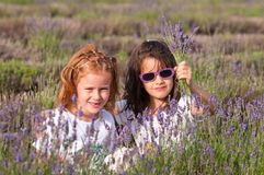 Young girls with lavender flowers. Two young girls with a bunch of lavender flowers Stock Images