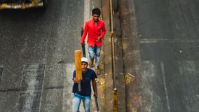 Youn guys cross the street in bombay with a cricket beat stock image