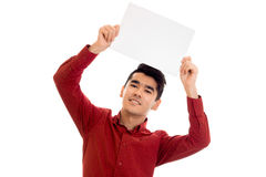 Youn Happy brunette male model in red shirt posing with empty placard in his hands and looking and smiling on camera Stock Images